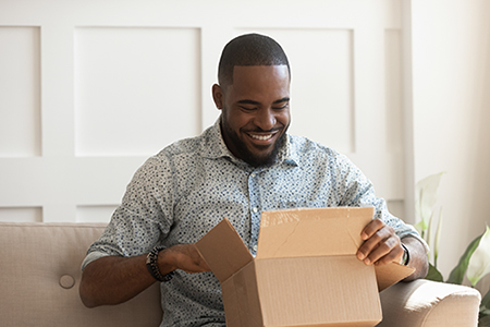 A man happily looks into an open parcel   Positieve customer experience